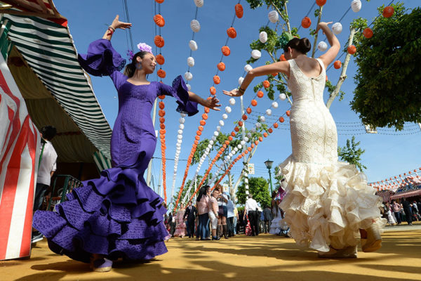 SEVILLE, SPAIN - APRIL 21:  Women Wearing The Traditional Flamenco Dresses, Often In Bright Colors, And Accessorized With Flower In Hair Dance Around Casetas (marquee Tents) At The 'Feria De Abril 2015', The Traditional Seville's Fair On April 21, 2015. The Fair Generally Begins Two Weeks After The Semana Santa, Or Easter Holy Week. Sevilla Society Parades Around The Fairground In Carriages Or On Horseback. There Are Also Daily Bullfights, Generally Considered The Best Of The Season. (Photo By Evrim Aydin / Anadolu Agency / Getty Images)