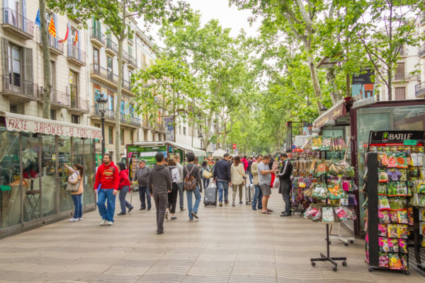 Barcelona, Spain - May 31, 2013: People Walking Near The Flower Stands In The Famous And Touristic La Rambla Street
